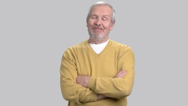 Smiling elderly man on grey background.