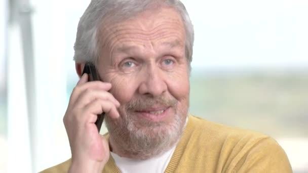 Detailní záběr starší muž mluví o telefonu.