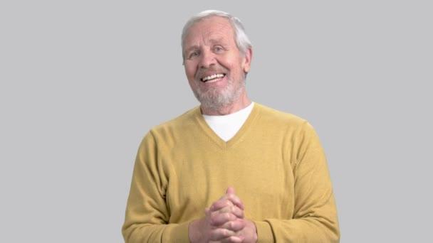Smiling elderly man talking at camera.