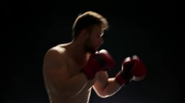 Young boxer is training on dark background.