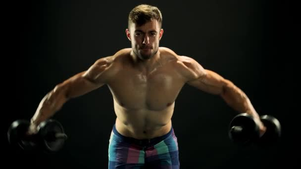 Muscular fitness man training with dumbbells.