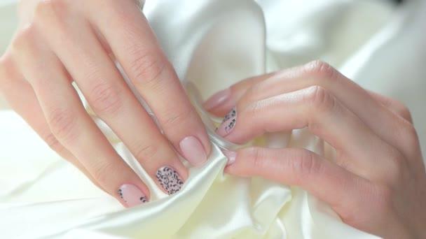 Gyengéd simogatása, fehér selyem női kezek.