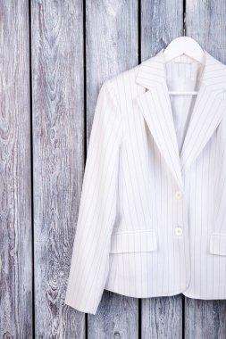 White suit jacket on hanger. Dark wooden background. Top view. stock vector