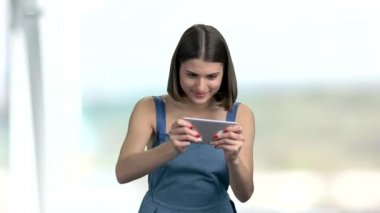 Funny young woman playing on smartphone.