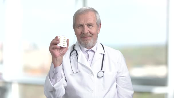 Senior doctor in white uniform showing pills.