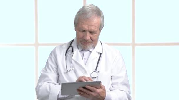 Starší lékař pracující na počítači tablet.
