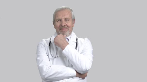Happy senior doctor, grey background.