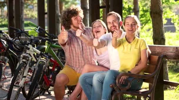 Young cheerful people gesturing thumbs up.
