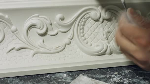 Worker cleaning gypsum ornament close up.