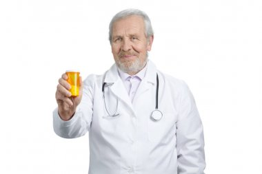 Old caucasian doctor holding can of pills.