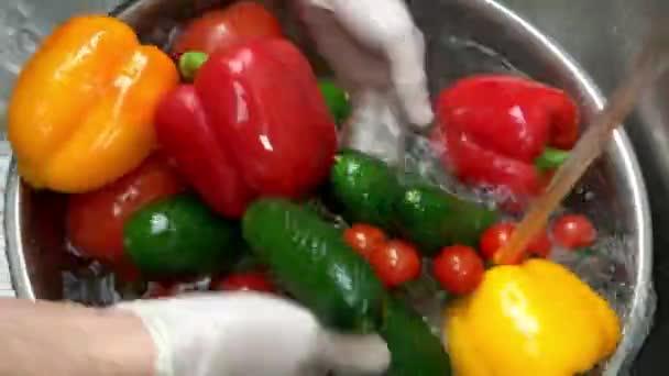 Hands washing colorful vegetables.