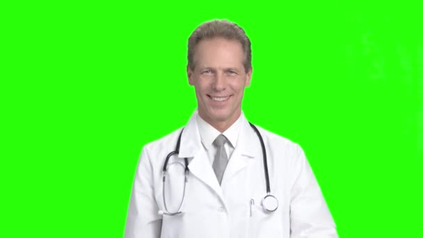 Mature doctor showing pills, green screen.