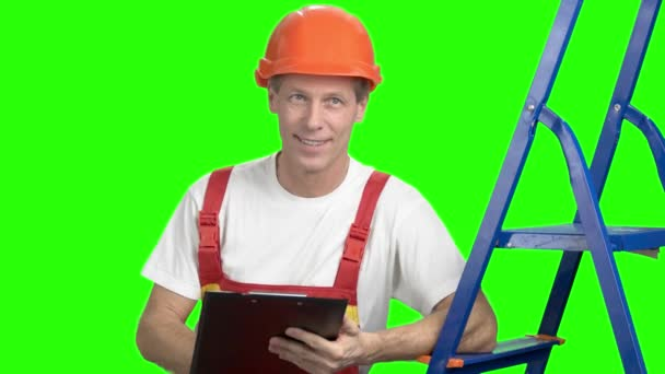 Male contractor writing on clipboard, green screen.