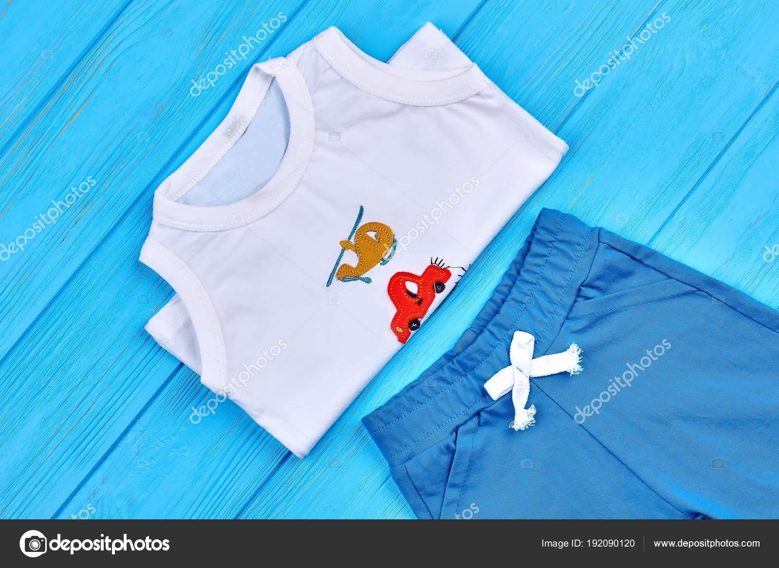 2b8e7e82670 Λίγο βαμβάκι αγόρι καλοκαιρινό κοστούμι. Νήπια αγόρια ξύλινο φυσικό ρούχα,  μπλε φόντο. Μωρό αγόρι casual ντύσιμο — Εικόνα από ...