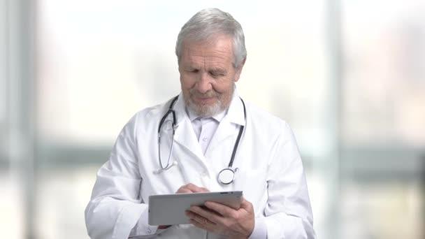 Lächelnder älterer Arzt mit PC-Tablet.