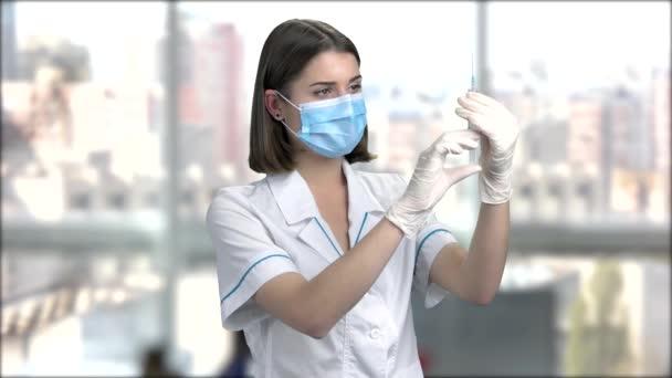 Mladá zdravotní sestra s lékařskou stříkačkou.