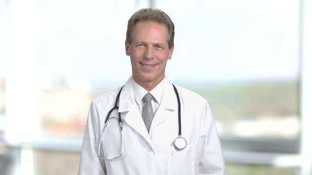 Usmívající se středním věku lékař portrét, pohled zepředu.