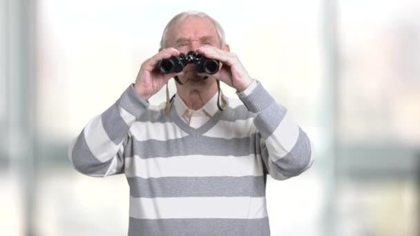 Öreg ember belenéz a távcső.
