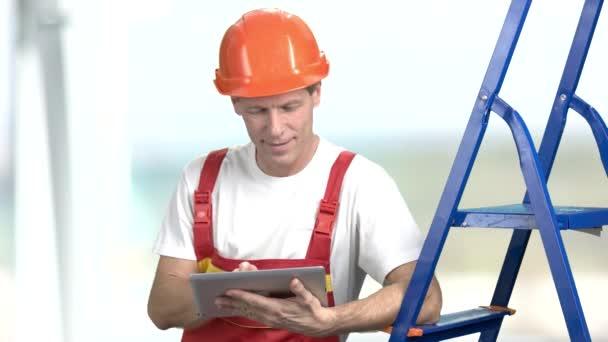 fröhlicher Vorarbeiter mit PC-Tablet.