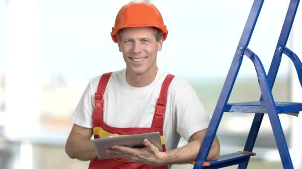 Šťastný úsměv inženýr, rozostřené pozadí.