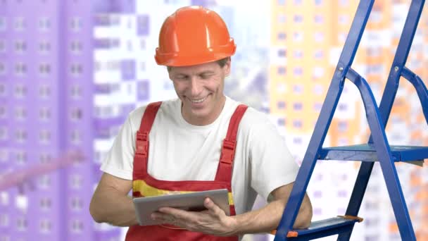 Smiling foreman on buildings background.