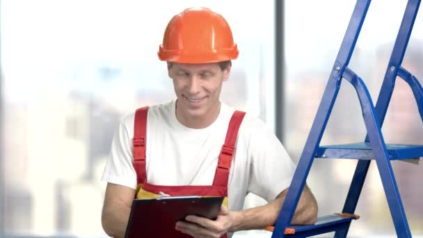 Smiling builder writing on clipboard.