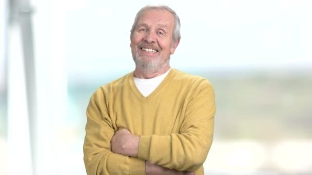 fröhlicher älterer Mann mit verschränkten Armen.