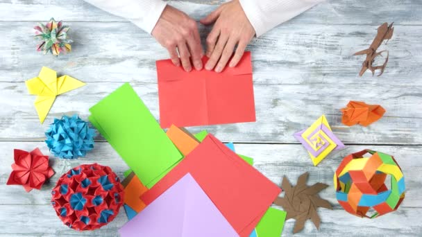 Person folding red paper sheet.