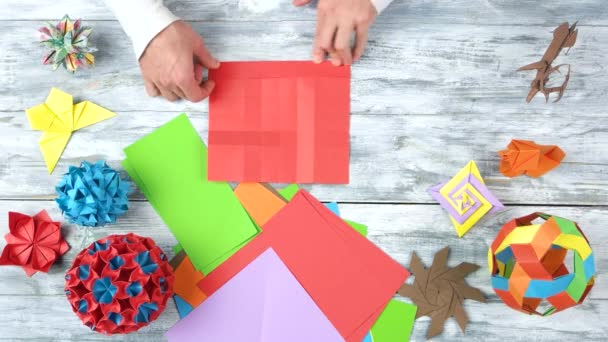 Origami projects on white wooden background.