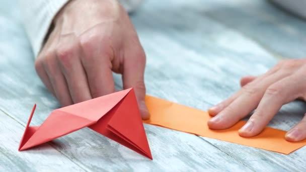 Close up man folding origami figure.