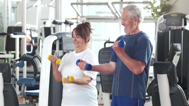 Pár seniorů cvičení s činkami
