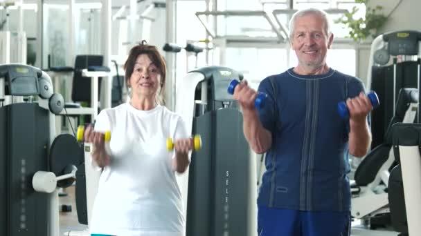 Pár seniorů, tréninky v tělocvičně.
