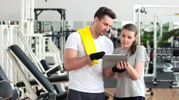 Young people using digital tablet at gym.