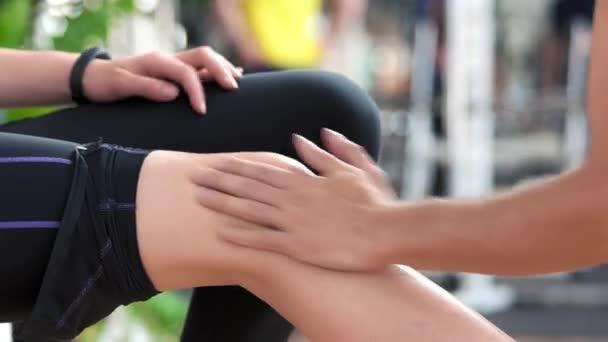 Žena příjem koleno masáž v tělocvičně