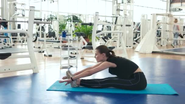 Girl stretching on mat at gym.