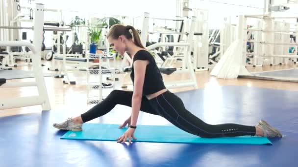 Athletic woman doing stretching at gym.