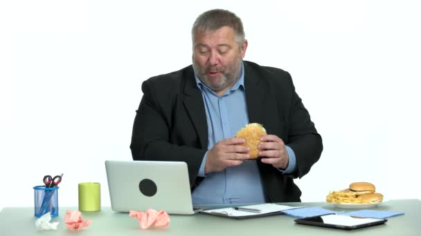 Businessman works at a computer and eats fast food.