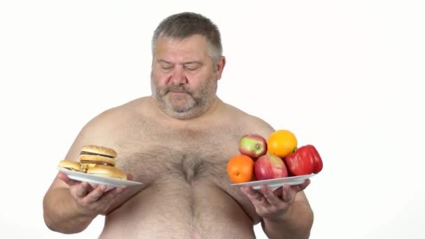Fettleibige Männer wählen zwischen Sandwich und Früchten.