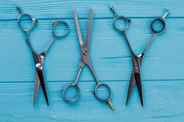 Set of hairdressing scissors on blue wooden background. Three metal barber scissors. stock vector