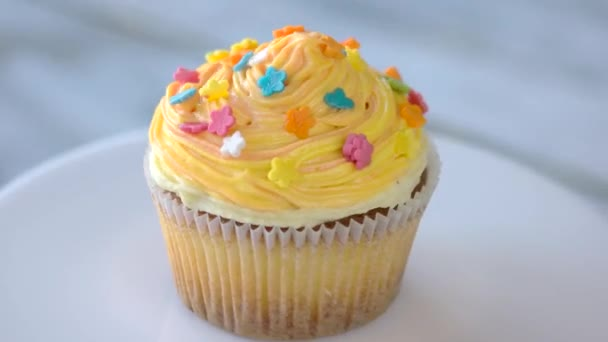 Cupcake with orange cream cheese frosting.