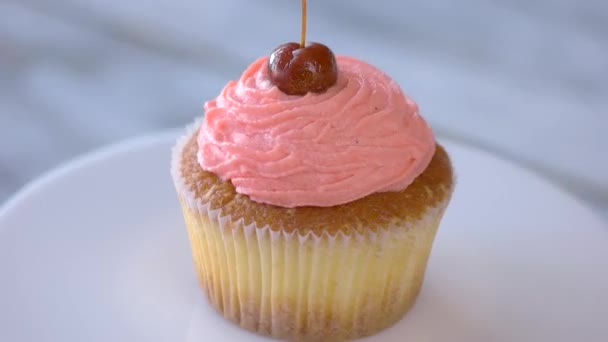 Cherry cupcake on white plate.