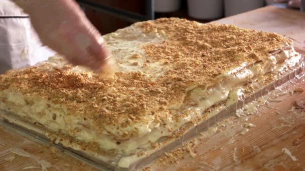Confectioner preparing layered cake.