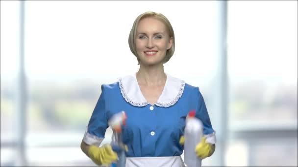 Lächelndes Zimmermädchen mit Flaschen Waschmittel.