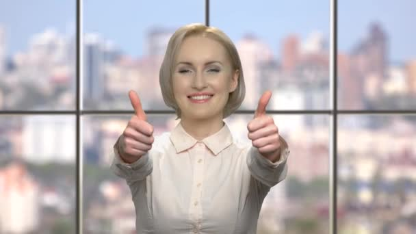 Attractive business woman gesturing thumb up.