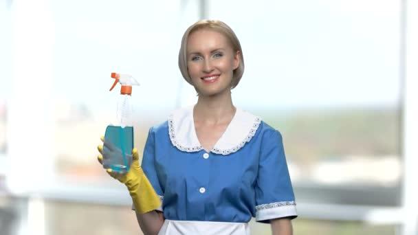 hübsch lächelndes Hausmädchen zeigt Putzspray.