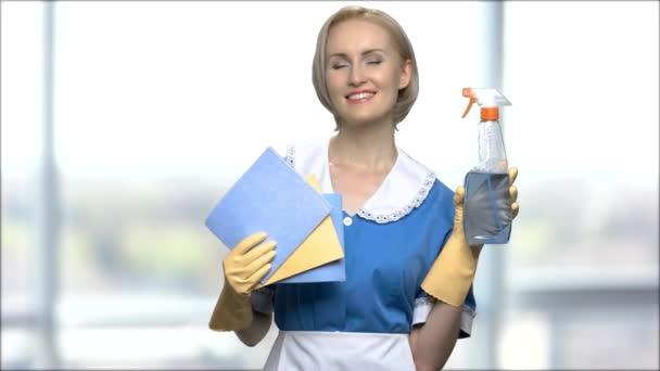 Hübsches Zimmermädchen mit Putzspray und Lumpen.
