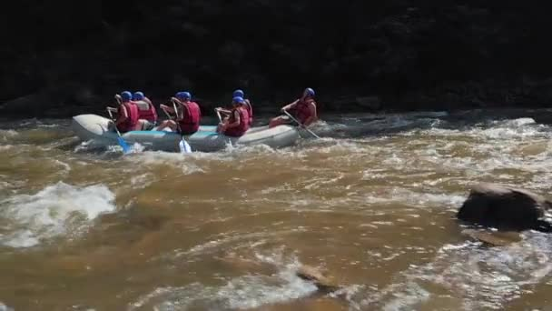 Side view of people on kayaks rafting on mountain river.