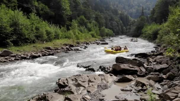 Group of young people rafting along a mountain river.