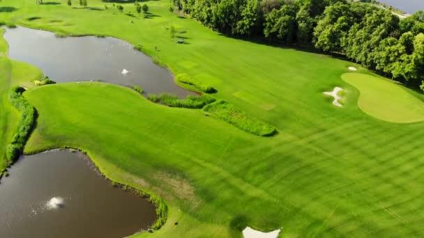 Široké zelené golfové hřiště s umělými rybníky.