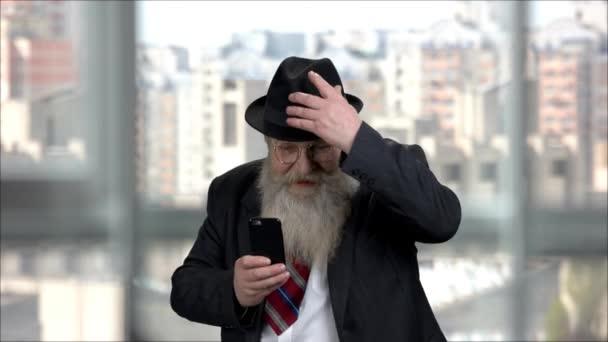 Ausdrucksstarker, fröhlicher, langbärtiger alter Mann, der mit seinem Handy fotografiert.